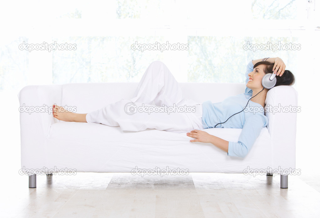 Young woman on couch and listen to the music — Stock Photo #1929654