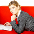 Woman on red couch - Stock Photo