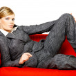Woman on red couch — Stock Photo