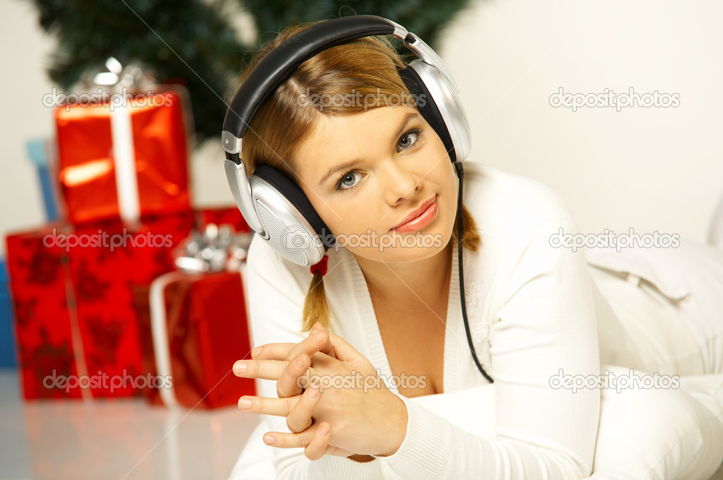 Young beautiful woman next to christmas tree and presents listen to music in headphones — Stock Photo #1932081