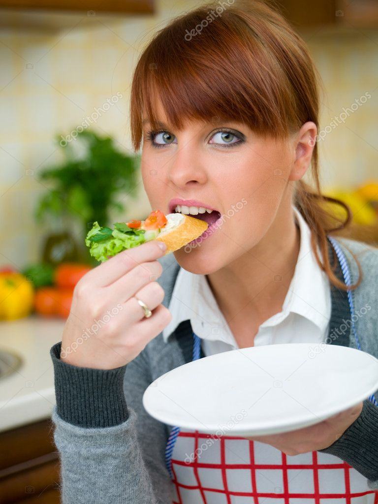 Beautiful woman in kitchen eating sandwich — Stock Photo #1933659
