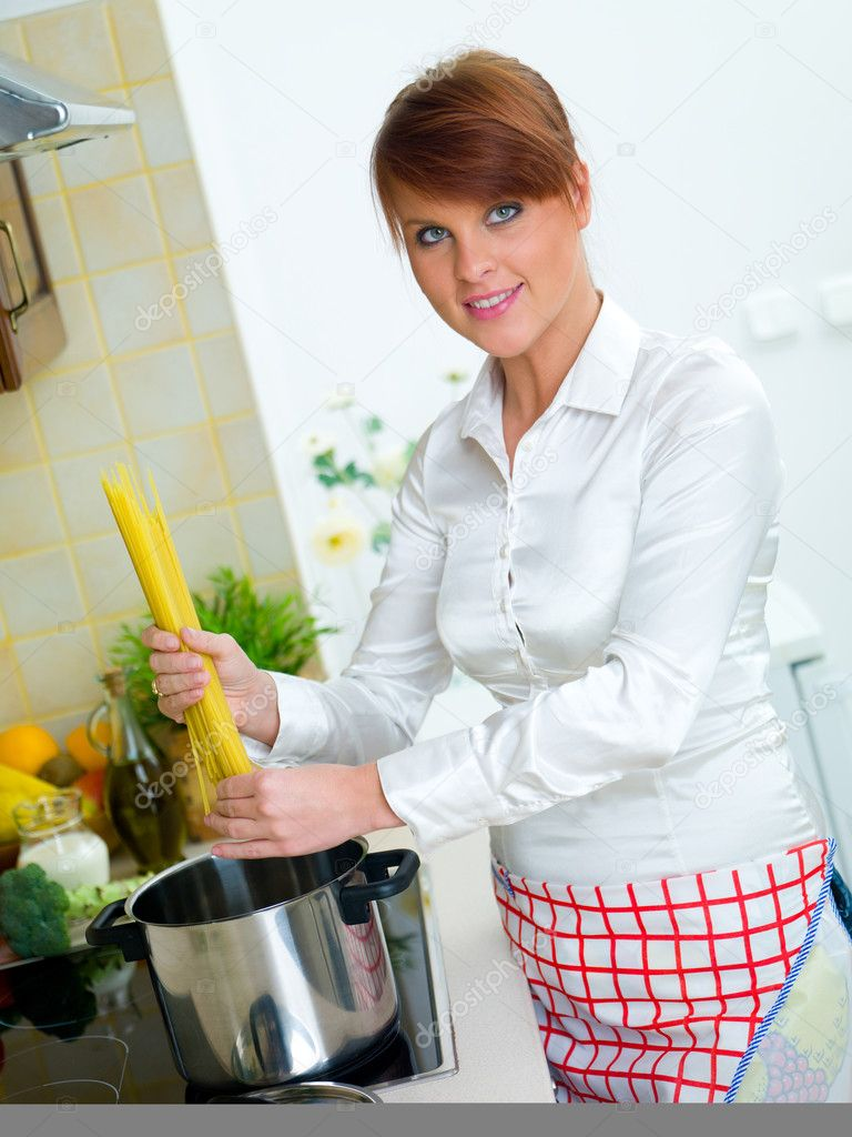 Beautiful woman in kitchen is preparing spaghetti — Stock Photo #1933816