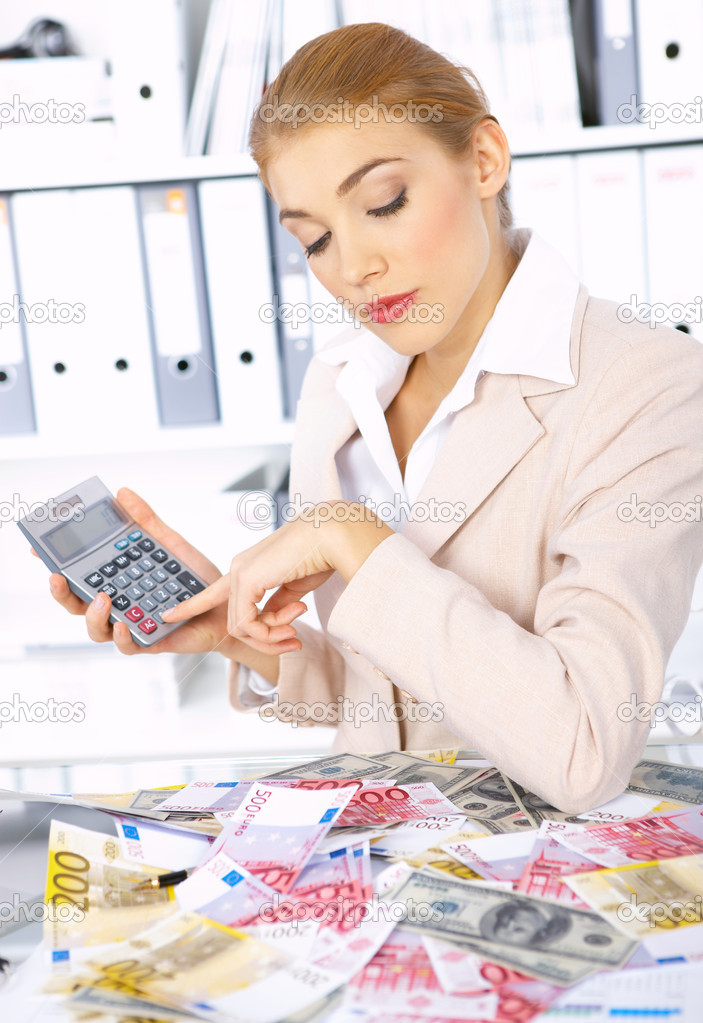 Beautiful accountant using calculator to count cash   Stock Photo #1949500