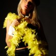 Pretty blonde women on black background wearing hat and yellow feathers - Stock Photo
