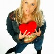 Blonde sexy girl holding a red velvet heart — Stock Photo