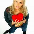 Blonde sexy girl holding a red velvet heart - Stock Photo