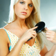 Sexy blonde young woman brushing hair — Stock Photo