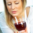 Pretty young blonde woman with glass of red wine - Stock Photo