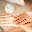 Young women applaying cream on her skin — Stock Photo