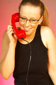 Pretty blonde young women with red classic phone — Stock Photo