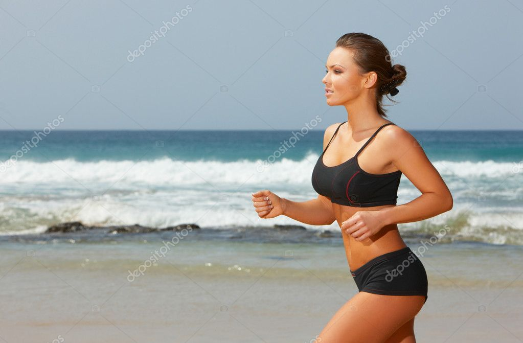 Young beautiful woman during fitness on sea beach  — Lizenzfreies Foto #1958247