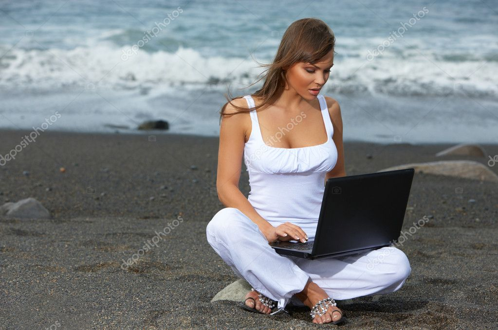 Beautiful woman on the beach working on laptop — Stock Photo #1958510