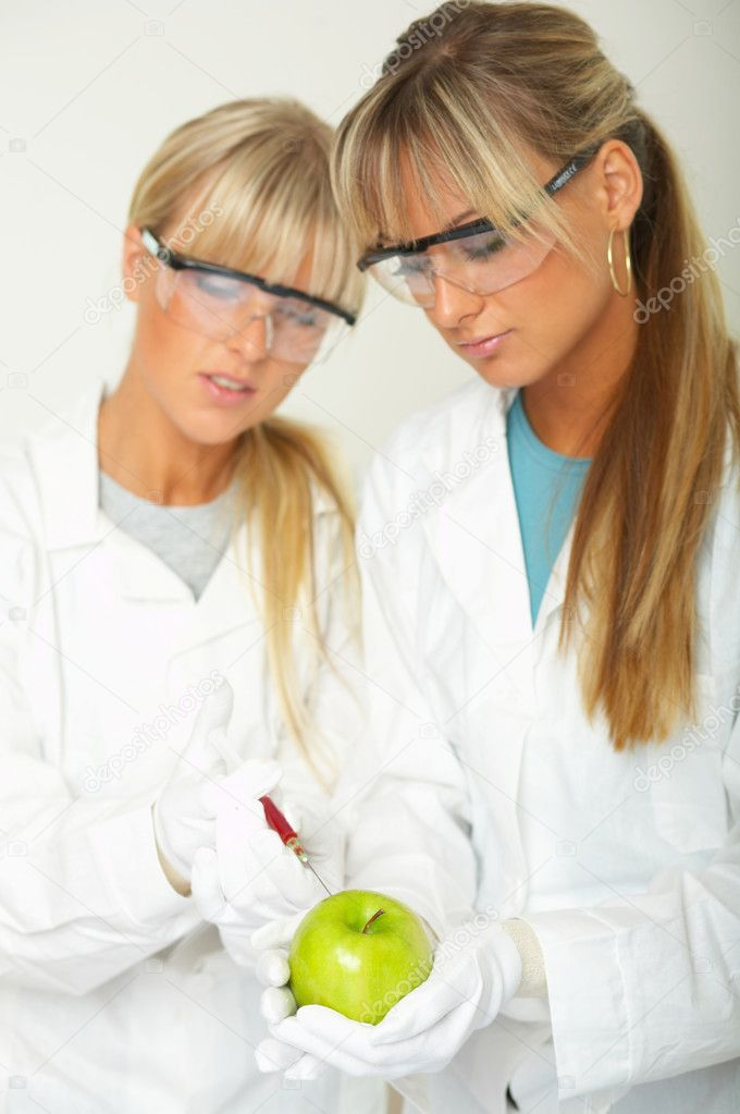 Female scientists injecting liquid into a apple — Stock Photo #1958642