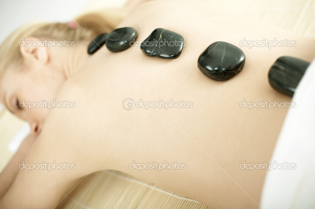 Young blond woman getting lastone treatment at spa — Stock Photo #1960691