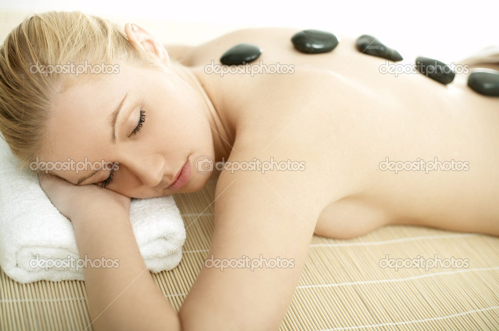 Young blond woman getting lastone treatment at spa — Stock Photo #1960731