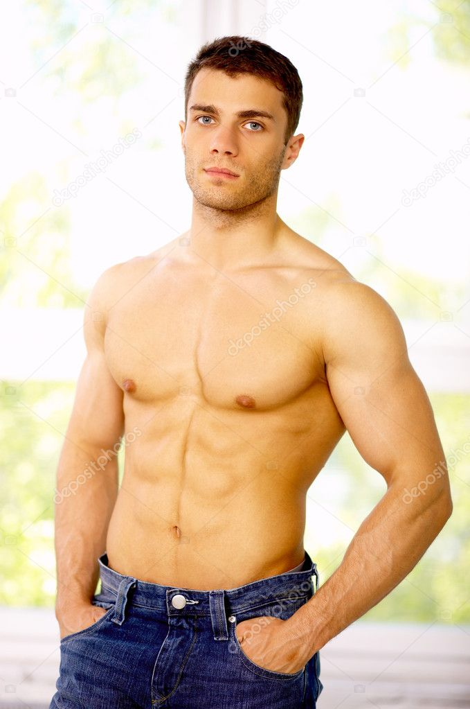 Muscular and tanned male standing near the window  Stock Photo #1962174