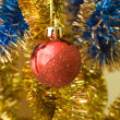 Red ball among a bright tinsel — Stockfoto
