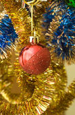 Red ball among a bright tinsel — Stock Photo