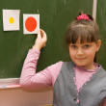 The schoolgirl standing at a blackboard — Stock Photo