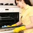 The girl on kitchen wipes an oven — Stock Photo