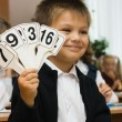 The boy shows cards with figures — Stock Photo