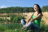 The beautiful young woman sits ashore — Stock Photo