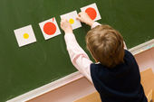 The pupil with cards at a blackboard — Stock Photo