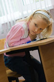 The girl sits at a school desk — Stockfoto