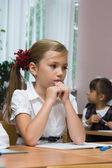 The sad girl sits at a school desk — Stock Photo