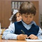 The boy in a dark blue waistcoat writes — Stock Photo