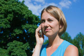The woman talks by a mobile phone — Stock Photo
