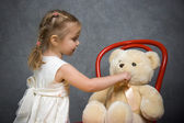 Little girl plays with teddy bear — Stock Photo