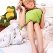 Girl oversleeping and sitting on bed — Stock Photo
