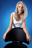 Beautiful blonde woman standing near the office chair on a blue background — Stock Photo