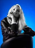 Beautiful blonde woman on a blue background — Stock Photo