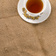 Red tea and burlap background — Stok fotoğraf