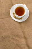 Red tea and burlap background — Stock Photo