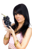 Brunette with black grapes — Stock Photo