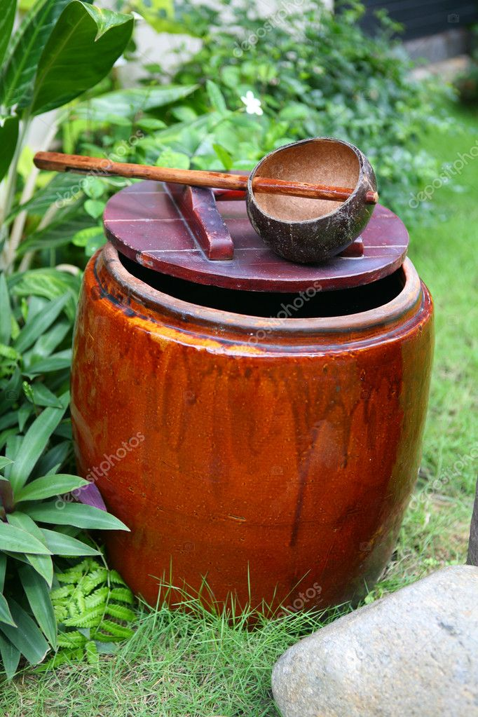 Ceramic cask of water and dipper on wood cover — Stockfoto #1833994