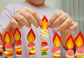 Child hands putting a paper flame — Stock Photo