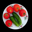 Red tomatoes and green cucumbers - Stock Photo