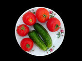 Red tomatoes and green cucumbers — Stock Photo