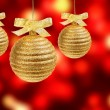 Three golden balls on red background — Stockfoto