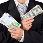 Businessman holding dollars and euros, i — Stock Photo