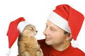 Young man and cat in Santa's hat — Stock Photo