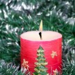 Red candle and green tinsel - Stock Photo