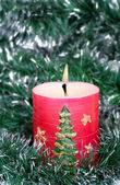 Red candle and green tinsel — Stock Photo