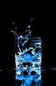 Ice cube splashing into glass of water — Stock Photo