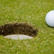 Stock Photo: Golf ball very close to a hole