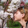 Woman smelling spring flowers outdoors — Stockfoto